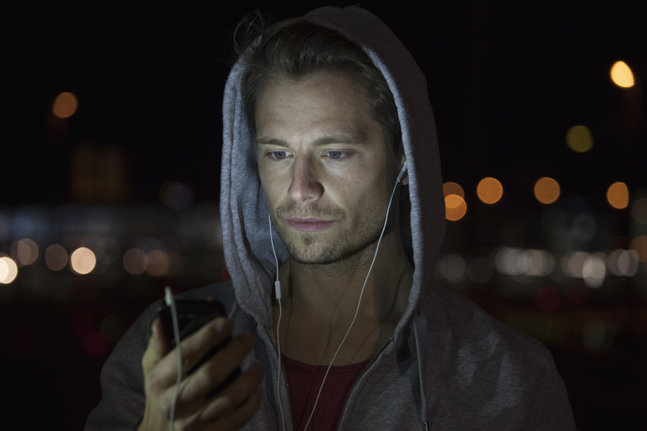 Portrait of young man wearing hooded jacket listening music at night